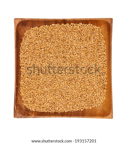 Wheat in a wooden bowl on white background
