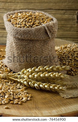 Wheat in small burlap bag on wooden background - stock photo