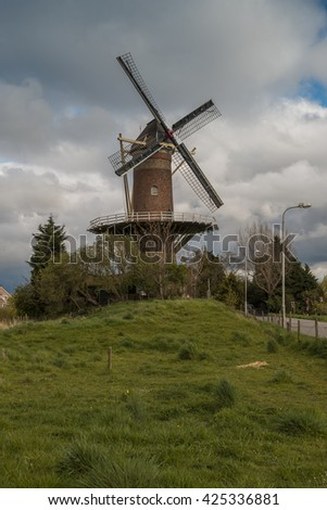 Wheat mill in Wolphaartsdijk, The Netherlnads during tempestuous spring weather - stock photo
