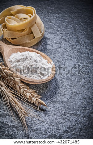 Wheat rye ears wood spoon flour pasta fettuccine on black background food and drink concept. - stock photo