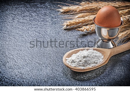 Wheat rye ears wooden spoon flour eggcup boiled egg on black background. - stock photo