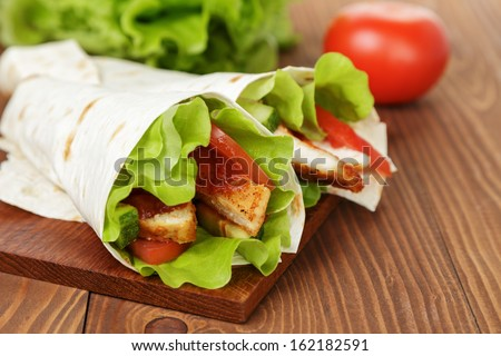 wheat tortilla with chicken and vegetables on wood board - stock photo
