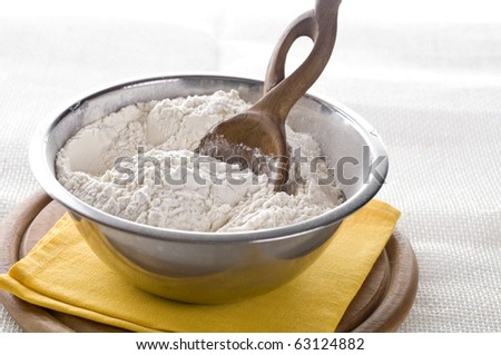Wheat  white flour in cooking bowl  with wooden spoon