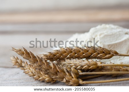 Wheat with flour on old wooden table - stock photo