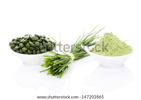Wheatgrass in powder, wheat grass blades, spirulina and chlorella pills isolated on white background. Healthy living. - stock photo