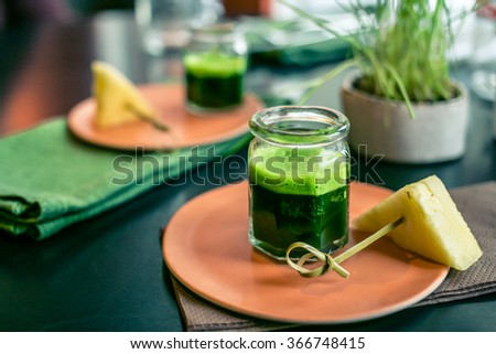 Wheatgrass juice with piece of pineapple on the plate in a restaurant - stock photo