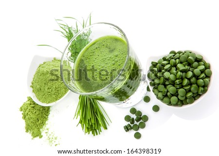 Wheatgrass powder, green chlorella pills and spirulina green juice on white background isolated. Natural healing. Alternative medicine.  - stock photo