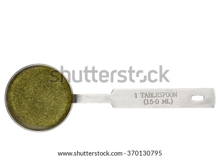wheatgrass powder in a metal measuring tablespoon isolated on white - stock photo