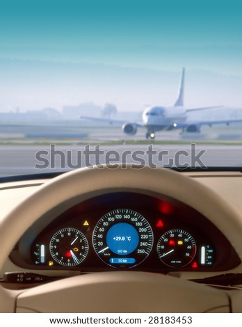 Wheel and dashboard of a car and view of airport - stock photo
