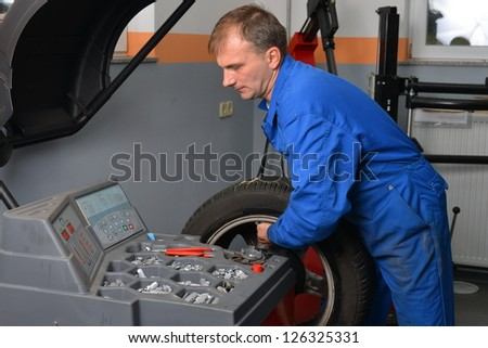 Wheel Balancing, Auto mechanic spins a car wheel as he waits for the machine to tell him he's reached the right spot to add a balancing weight.