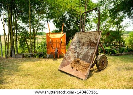 Wheel barrow on the grass in the garden - stock photo