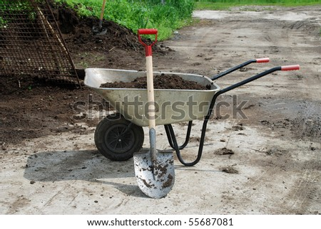 wheel barrow on the land at the county with land and shovel - stock photo