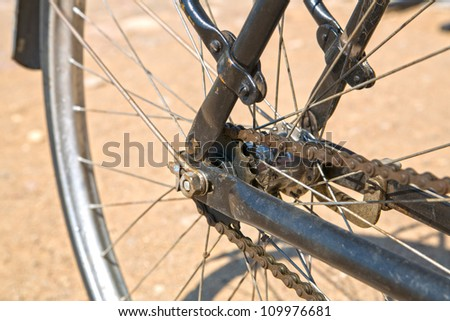 Wheel from bicycle with its speen dusty chain - stock photo