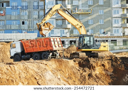 wheel loader and excavator machine loading dumper truck at construction area sand quarry - stock photo