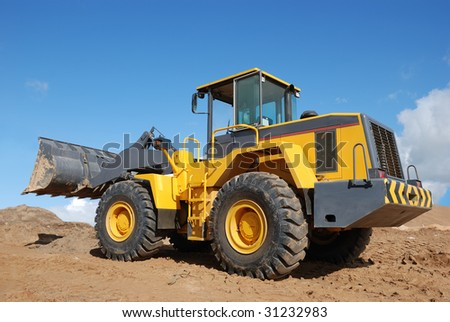 Wheel loader bulldozer with bucket outdoors over blue sky - stock photo