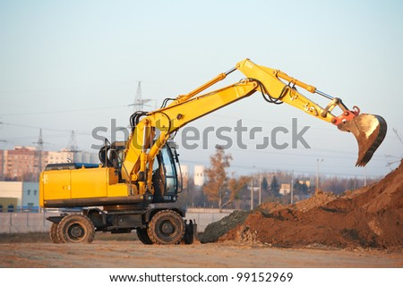wheel loader excavator machine doing earthmoving work at sand quarry - stock photo