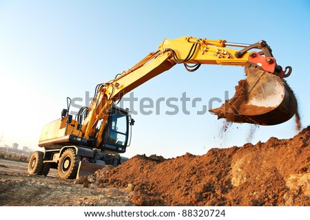 wheel loader excavator machine loading doing earthmoving work at sand quarry - stock photo