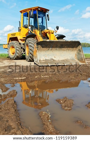 wheel loader excavator machine standing in dirty place at quarry - stock photo