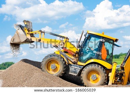 Wheel Loader Excavator unloading Gravel or Sand during Earth Moving Works at Construction Site - stock photo