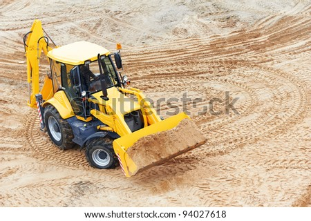 Wheel loader Excavator with backhoe loading sand at eathmoving works in construction site - stock photo