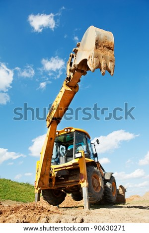 Wheel loader Excavator with backhoe unloading sand at eathmoving works in construction site - stock photo