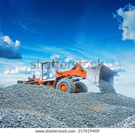 wheel loader excavator working with  gravel on big pile - stock photo