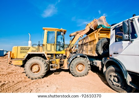 Wheel loader machine loading into dumper truck tipper soil at construction site - stock photo
