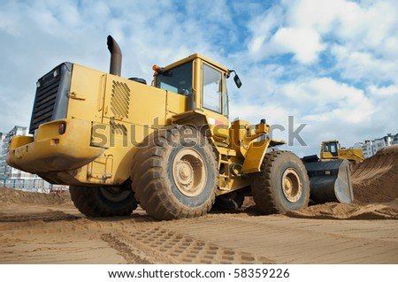 Wheel loader machine loading sand at eathmoving works in construction site - stock photo