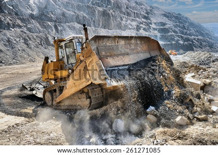 Wheel loader machine unloading rocks in the open-mine of iron ore - stock photo