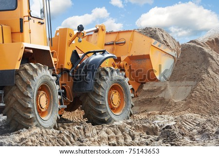 Wheel loader machine unloading sand at eathmoving works in construction site - stock photo