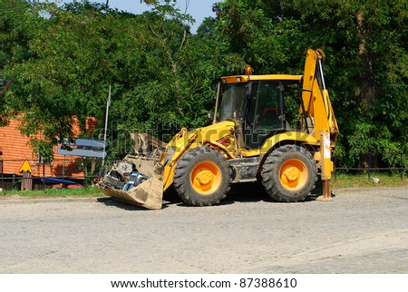 Wheel loader machine unloading sand at eathmoving works in construction site. - stock photo