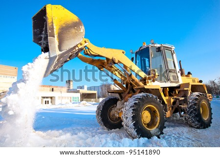 Wheel loader machine unloading snow during municipal works crews - stock photo