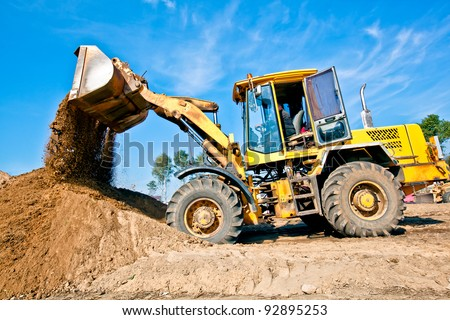 Wheel loader machine unloading soil during earthmoving works at construction site - stock photo
