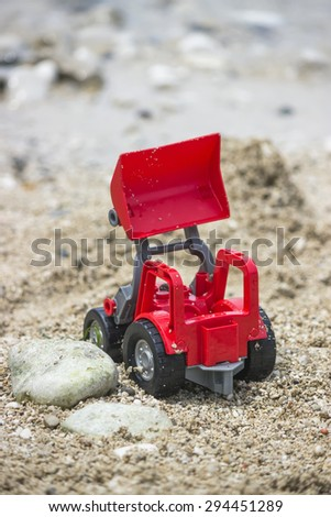 Wheel loader toy on the beach. Selective focus and shallow dof. - stock photo