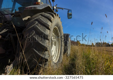 Wheel of tractor in rural landscape on sunny day in autumn
