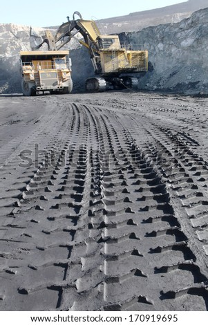 wheel track and foot print on clay road in iron mine - stock photo