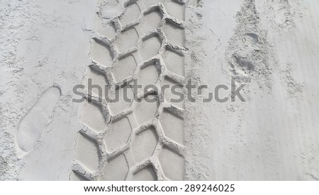 Wheel track and footprints on the sandy beach - stock photo