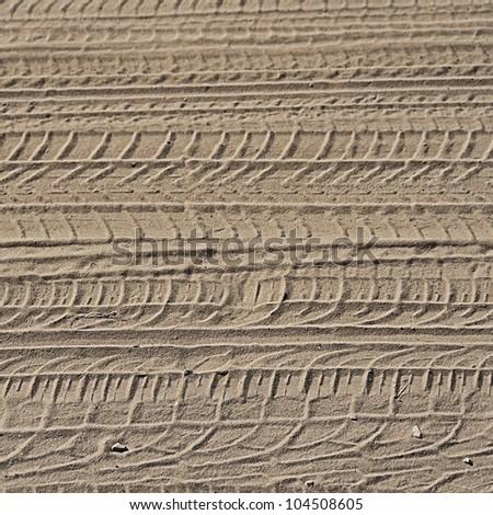 wheel tracks in the sand. - stock photo