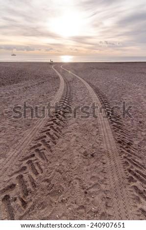 Wheel Tracks in the Sand of a Sandy Beach Desert - stock photo
