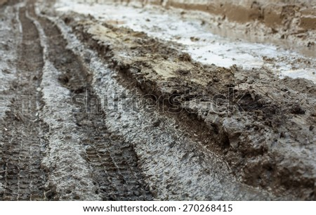 Wheel tracks on the muddy dirt road after the rain. - stock photo