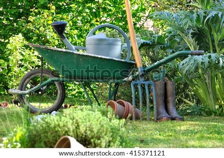 wheelbarrow and gardening tools in vegetable garden  - stock photo