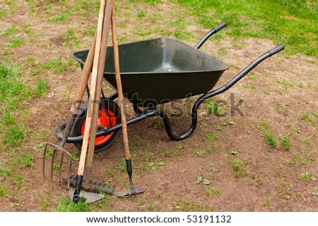 Wheelbarrow and some gardening equipment in a garden.