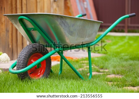 Wheelbarrow cart in a garden - stock photo