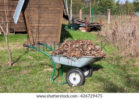 Wheelbarrow for the carriage compost on the rural land - stock photo