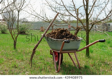 Wheelbarrow full of manure and pitchfork in garden - stock photo