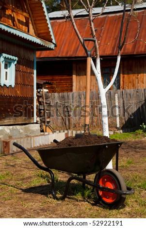 Wheelbarrow full of soil in a garden - stock photo