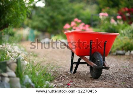 Wheelbarrow in a blooming garden. Shallow DOF. - stock photo
