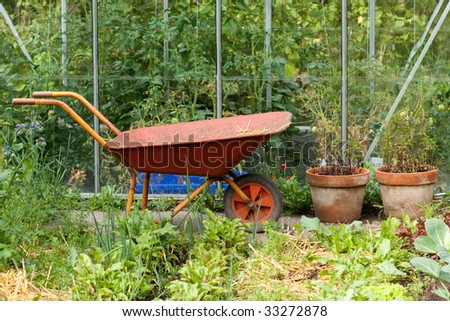 Wheelbarrow in front of  the greenhouse - stock photo