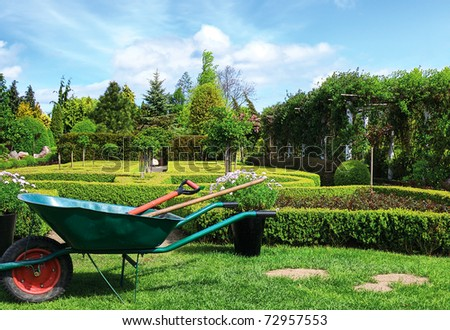 Wheelbarrow in the garden - stock photo