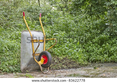 Wheelbarrow standing upright on concrete with foliage behind - stock photo